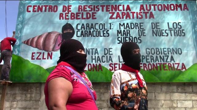 "Dos zapatistas frente a un cartel que reza ""Centro de resistencia autonoma rebelde zapatista"""