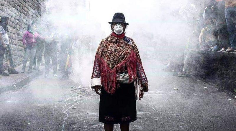 Una mujer con traje tradicional boliviano y mascarilla posa frente al humo de gases lacrimogenos
