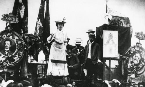Fotografía antigua, una mujer da un mitin mientras varios hombres detrás suyo la escuchan