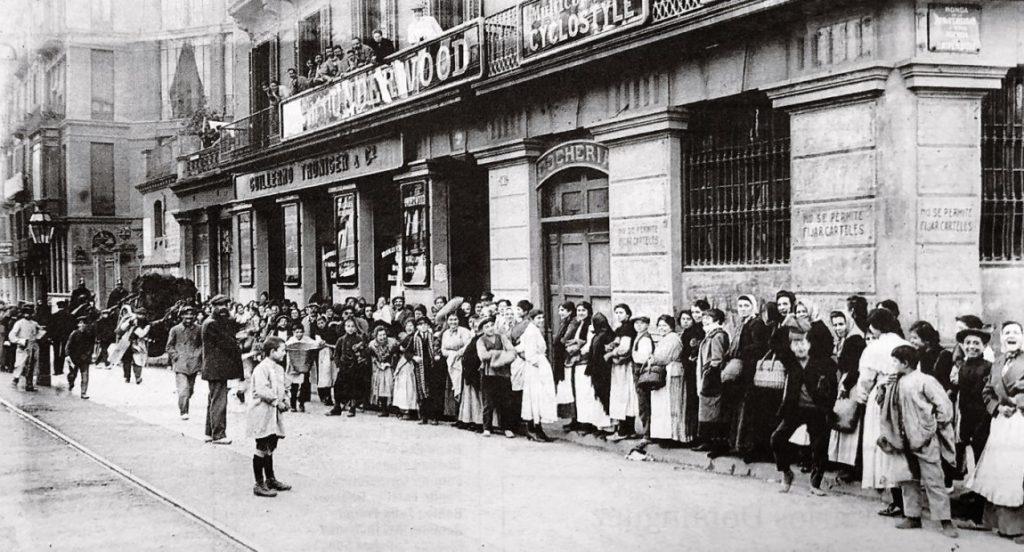 Fotografía antigua, decenas de personas hacen cola frente a un edificio.
