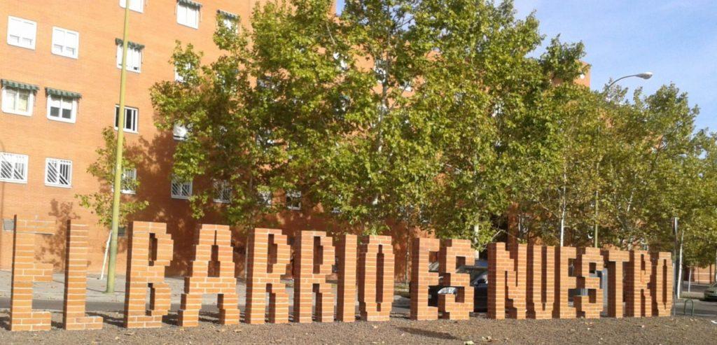 """Fotografia, se ve el texto """"El barrio es nuestro"""" fabricado con letras de ladrillo"""
