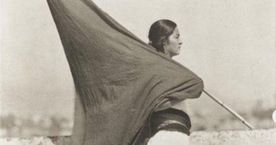 Fotografía antigua de una mujer sosteniendo una bandera negra