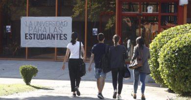 """Cuatro estudiantes de espaldas se dirigen a la entrada de una universidad junto a la cual hay una pancarta en la que se puede leer """"La universidad para las estudiantes"""""""