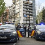 Fotografia de dos coches de la policia nacional aparcados y tres agentes a su lado